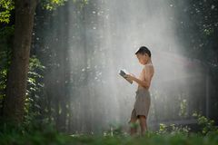 Asian students reading books in Thailand countryside, Rural children are reading a book at the forest.Book knowledge is important. For Genes in the rural areas stock image