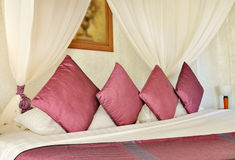 Asian style bed with nice silk pillows. Asian style bed with nice red silk pillows Royalty Free Stock Photography