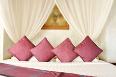 Asian style bed with nice silk pillows. Asian style bed with nice red silk pillows Royalty Free Stock Images