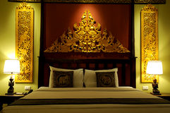Asian style bedroom. A well decorated bedroom furnished in a Thai or Asian style Stock Image