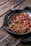 Asian style Beef carpaccio. With soy sauce, chive onion, black sesame, served on vintage metal tray with textile napkin and chopsticks over old wooden plank Stock Images