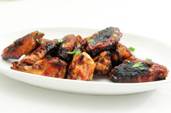 Asian style chicken wings. Juicy asian style chicken wings on a white plate with a white background Stock Photo