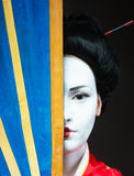 Asian style female portrait. Closeup portrait of a woman in geisha makeup covering half of her face with a big fan royalty free stock photos