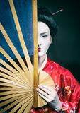 Asian style female portrait. Woman in geisha makeup covering half of her face with a big fan royalty free stock photo