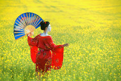 Asian style female portrait. Asian style portrait of a woman in geisha makeup with a decorative wall fan stock photo