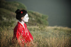 Asian style female portrait. Portrait of a woman in geisha makeup sitting by the riverside stock photo