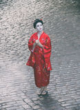 Asian style female portrait. Portrait of a woman in geisha makeup standing on a cobblestone pavement, view from above stock images
