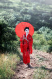 Asian style female portrait. Portrait of a woman in geisha makeup walking in the countryside stock image