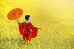 Asian style female portrait. Woman in geisha makeup walking with the umbrella in the fields stock photos