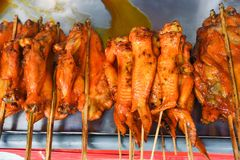 Asian style grilled chicken wing on tray wooden background - Thai roasting chicken skewer sticks royalty free stock photography