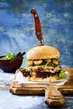 Asian style salmon burger with grilled shrimps, seaweed, lettuce and spicy sriracha mayo sauce served on rustic wooden board. Stock Image