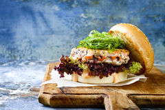 Asian style salmon burger with grilled shrimps, seaweed, lettuce and spicy sriracha mayo sauce served on rustic wooden board. Royalty Free Stock Photography