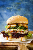 Asian style salmon burger with grilled shrimps, seaweed, lettuce and spicy sriracha mayo sauce served on rustic wooden board. Stock Photography
