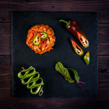 Asian-style stir-fry cooking hot vegetable saute on slate, wooden background, eggplants, chili pepper, cucumber Royalty Free Stock Images