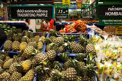 Asian supermarket shelf: pile of pineapples, bananas and other fruits. Thai and English market Royalty Free Stock Image