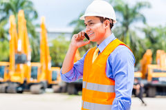 Asian supervisor telephoning on construction site. Asian foreman telephoning with mobile phone of building site or mining or rental company Royalty Free Stock Photography