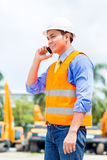 Asian supervisor telephoning on construction site. Asian foreman telephoning with mobile phone of building site or mining or rental company Royalty Free Stock Photos