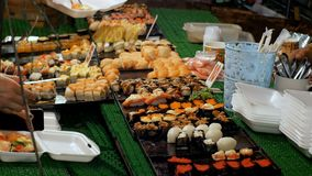 Asian sushi on the counter in the night food market of Jomtien. Pattaya, Thailand