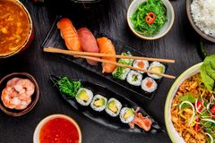 Asian Sushi variation with many kinds of meals. Kari rice, soup and vegetable. Top view, served on black stone royalty free stock photos
