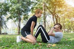 Asian sweet couple exercising together with smile on their faces on soft grass encircle with nature and warm light from the sun. Asian sweet couple exercising Stock Photos