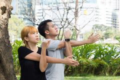 Asian sweet couple warm up their bodies by stretching arms before morning jogging exercise in the park. Asian sweet couple warm up their bodies by stretching stock image