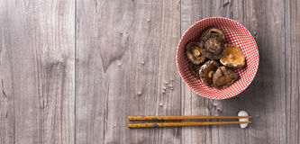 Asian table with chopsticks and dried shiitake mushrooms in a bowl. Asian table japanese style prepared with chopsticks and dried shiitake mushrooms on wood Royalty Free Stock Photography