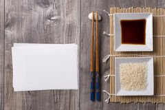 Asian table with chopsticks, soy sauce and rice and white note Royalty Free Stock Photo