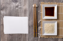 Asian table  with chopsticks, soy sauce and rice and white note. Asian table prepared with chopsticks, soy sauce and rice and white note for writing Stock Image