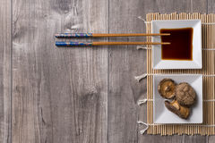 Asian table with chopsticks, soy sauce and shitake mushrooms. Asian table prepared with chopsticks, soy sauce and shitake mushrooms on bamboo Stock Image