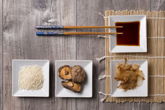 Asian table with ingredients and sticks. Asian table, japanese style, with chopsticks, soy sauce, bonito flakes, shitake mushrooms and rice Stock Images