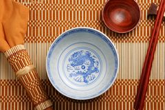 Asian tableware. Top view of asian tableware (bowl, sauce cup, chopsticks and napkin) on a bamboo tablemat royalty free stock photos