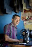 An Asian tailor work on the sewing machine, clothes hang on top. Royalty Free Stock Image