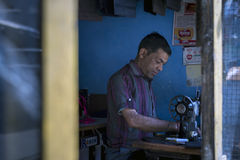 An Asian tailor work on the sewing machine, clothes hang on top. Stock Photography