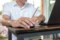 Asian tan skin holding wireless mouse on the vintage wood table and writting pencil with his left hand stock images