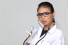 Asian Tan Skin Woman Doctor glasses in White Shirt suit with ste. Thoscope on neck, checking heart pulse pose, studio lighting gray background copy space for Stock Image