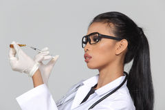 Asian Tan Skin Woman Doctor glasses in White Shirt suit with ste. Thoscope on neck, hold syringe needle injection pull out from medicine tube, studio lighting Stock Photography