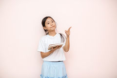 Asian tanned skin girl child portrait over pink wall background. Stock Images
