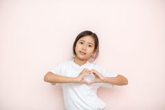Asian tanned skin girl child portrait over pink wall background, Stock Photos