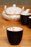 Asian tea cup with pot in the background Stock Photos