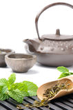 Asian tea set with fresh mint. Asian tea set with dried green tea and fresh mint over white Stock Photos