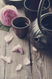 Asian tea set. Toned photo. Asian tea set and rose petals on the wooden background Royalty Free Stock Images