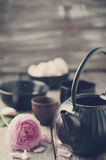 Asian tea set. Toned photo. Asian tea set and rose petals on the wooden background Royalty Free Stock Photo