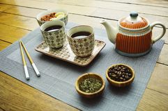 Asian tea set type on wood table with food and coffee stock image