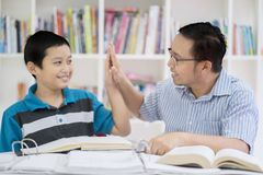 Asian teacher doing high five with his student. Portrait of an Asian male teacher doing high five with his student while studying together in the library Royalty Free Stock Photography