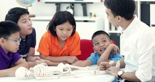 Asian teacher expanding to student in anatomy class with skeleton dummy . Asian teacher is expanding to student in anatomy class with skeleton dummy stock video