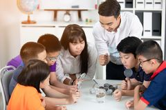 Asian teacher expanding to student in geology class with different of rock . stock photo