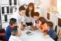 Asian teacher expanding to student in geology class with differe. Nt of rock Royalty Free Stock Photos