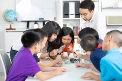 Asian teacher expanding to student in geology class with differe. Nt of rock Stock Images