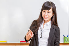Asian teacher in front of whiteboard pointing Stock Photos