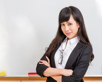 Asian teacher in front of whiteboard smiling Stock Photo